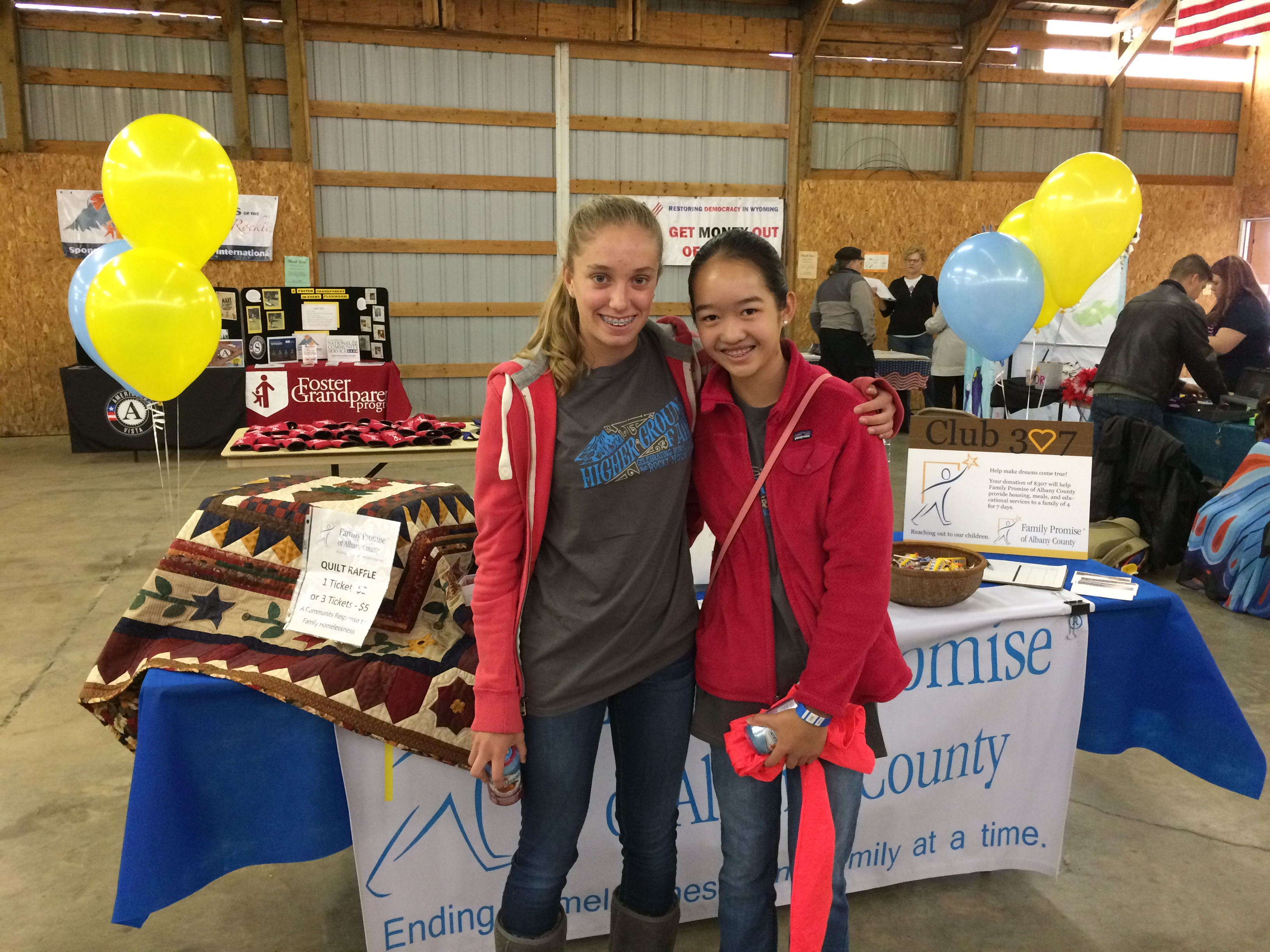 Two high school-aged girls standing in front of a table at a volunteer event
