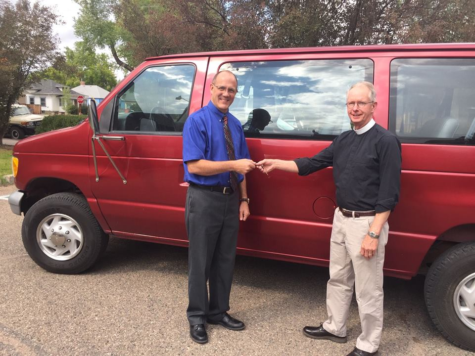 Two men standing in front of a red van donated to Family Promise of Albany County