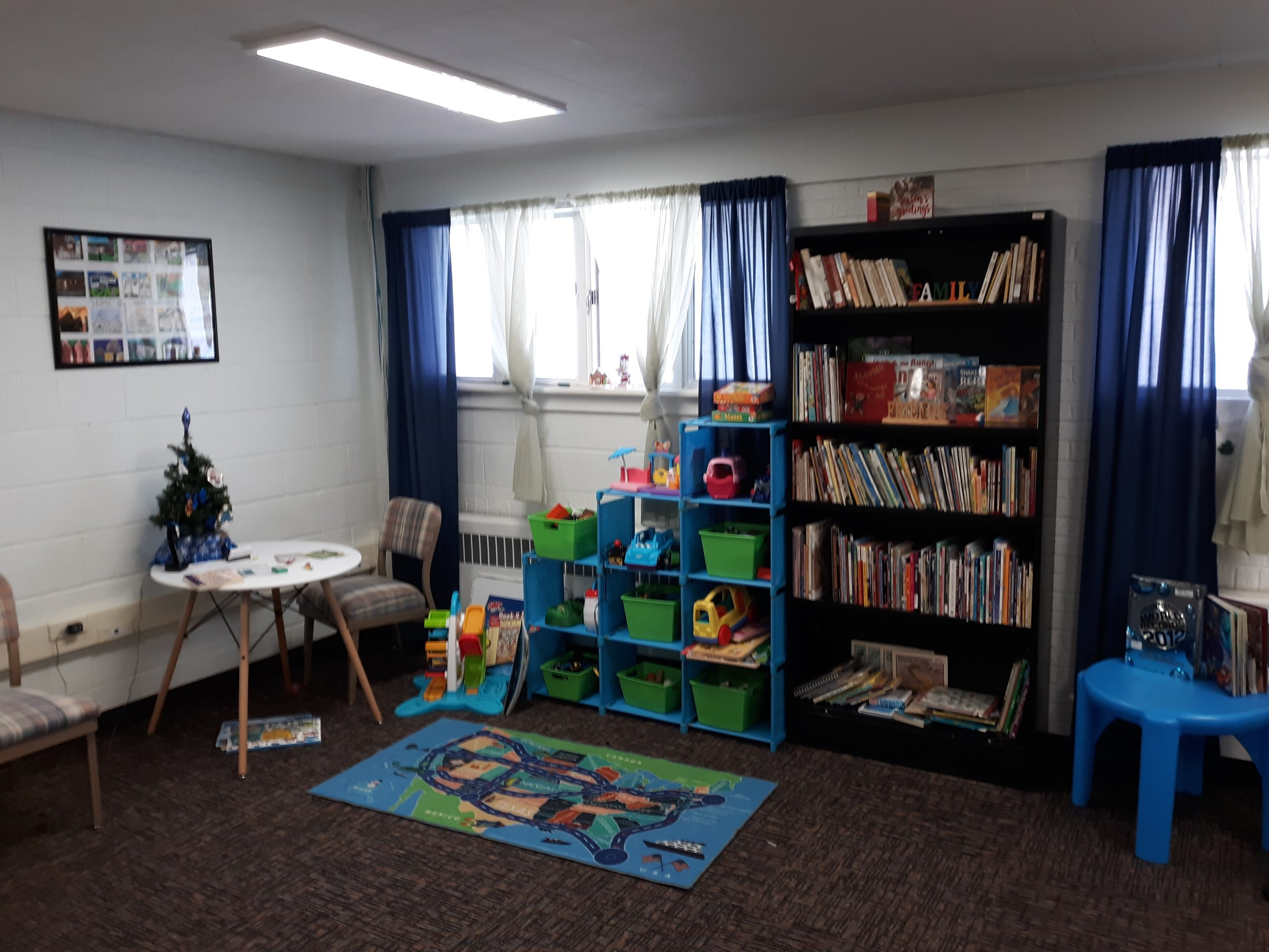 A room at the Family Promise of Albany County offices with children's toys, a table and chairs, and a bookcase full of books.